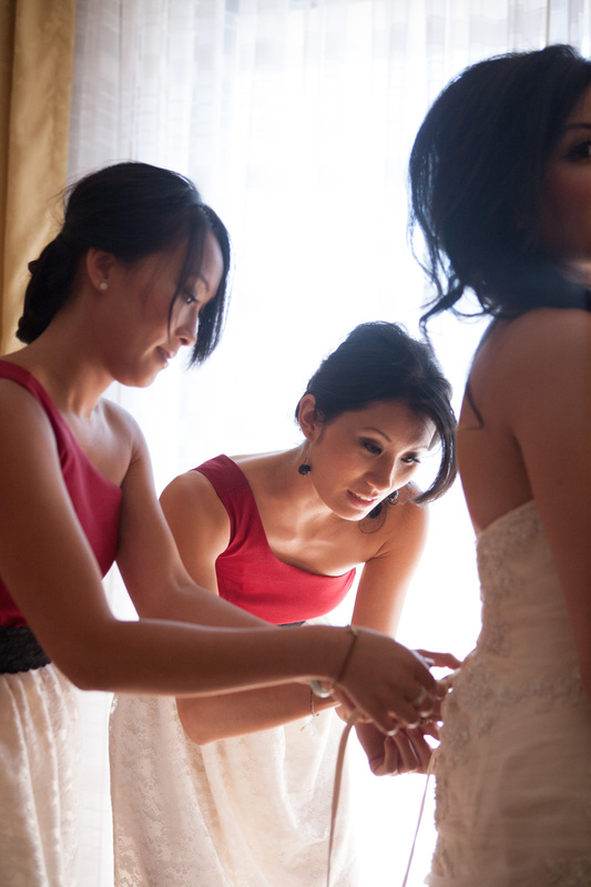 Bridesmaids lacing up the dress